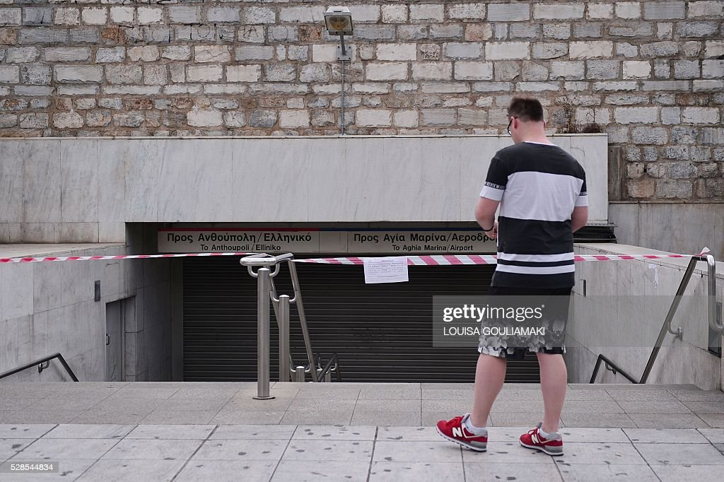 A Polish tourist reads an announcement informing about 48-hours strike as he stands at a closed metro station in Athens, on May 6, 2016. Greece's labour unions stage a two-day general strike to protest against controversial government plans to overhaul pensions and increase taxes to meet demands of its bailout creditors. / AFP / LOUISA