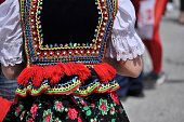 Polish heritage. Beautiful, colorful, handmade folk costume. Vest with beads, sequins, ribbons, red fringes and flowery skirt.