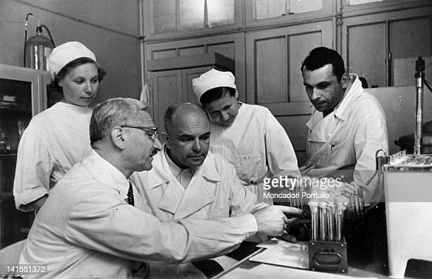 Polish virologist Albert Bruce Sabin showing some test tubes to Russian scientist Soloviev in a laboratory Sabin went to Soviet Union to explain his...