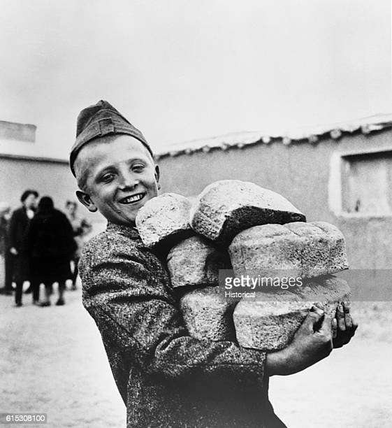 A Polish youngster smiles with his arms loaded down with bread made from flour supplied by the American Red Cross His smile is in anticipation of...