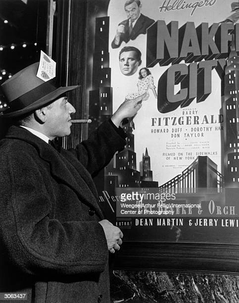 Polishborn American photographer Arthur 'Weegee' Fellig points to a poster for Mark Hellinger's 1948 film 'The Naked City' inspired by Weegee's...