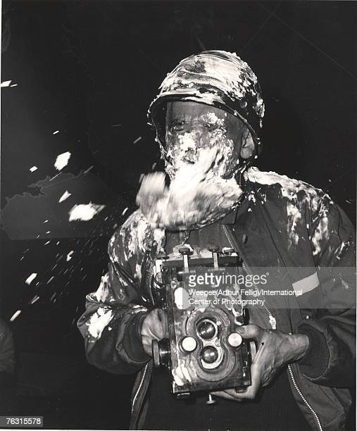 Polishborn American photographer Weegee camera in hand closes his eyes as a cream pie flies at him during filming on the set of the Stanley Kubrick...