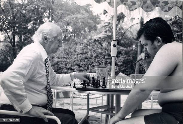 Polishborn Argentinian chess grandmaster Miquel Najdorf plays American grandmaster William Lombardy in a casual poolside game 1970s The former wears...