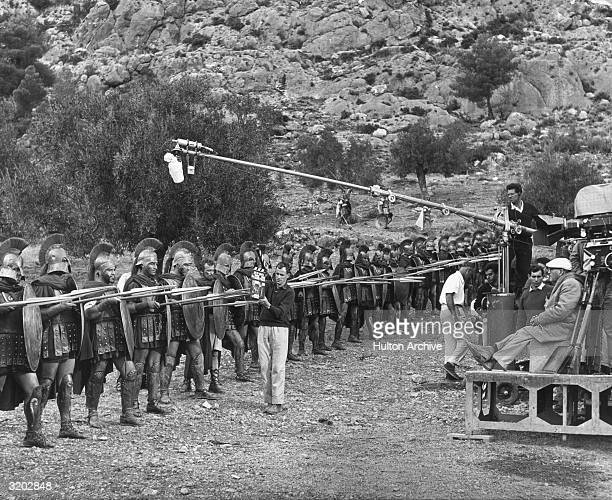 Polishborn director Rudolph Mate sits on a camera crane platform while filming a line of actors in ancient Greek armor on the set of his film 'The...