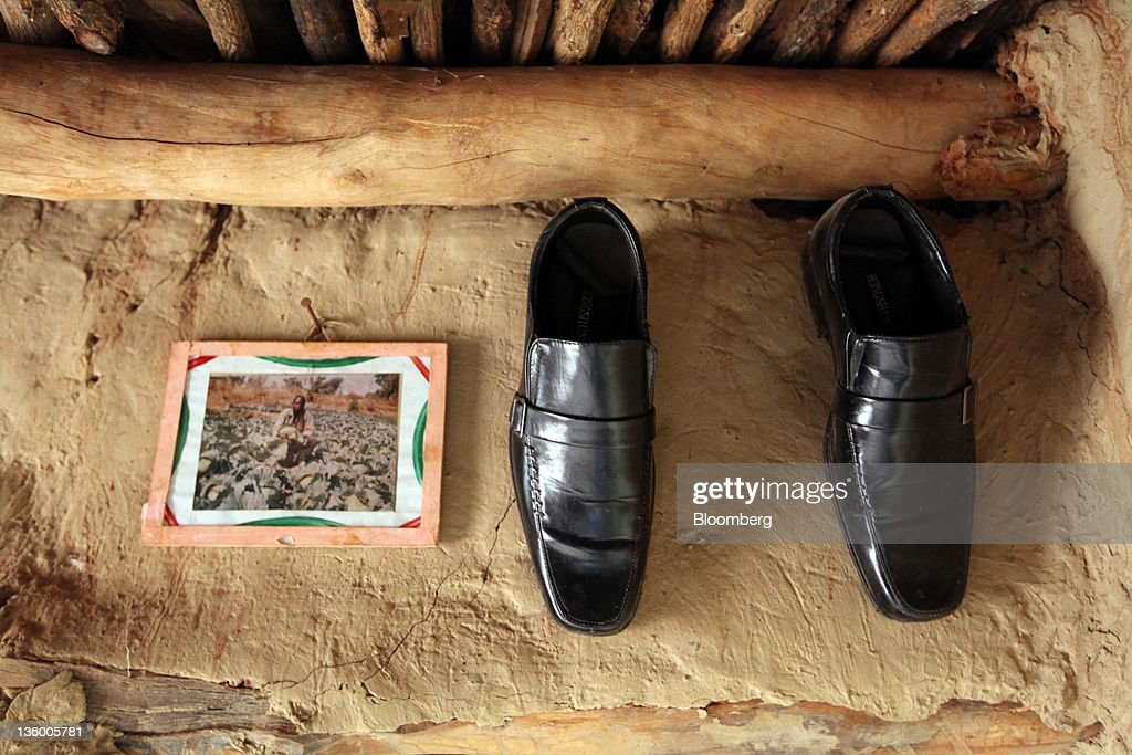 Polished shoes and a family photograph hang above a doorway in the home of cotton farmer Victorien Kamboule, and Clarisse Dabire, a child laborer, in Benvar, Burkina Faso, on Friday, Nov. 11, 2011. In Burkina Faso, one of the poorest countries in the world, where child labor is endemic to the production of its chief crop export, paying lucrative premiums for organic and fair traden cotton has -- perversely -- created fresh incentives for exploitation. Photographer: Chris Ratcliffe/Bloomberg via Getty Images