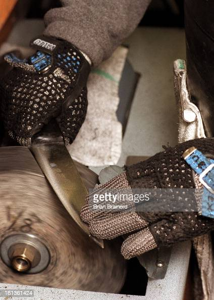 Polishing a sharpened knife can be dangerous so Darryl Hoffman wears chain gloves and chest protector