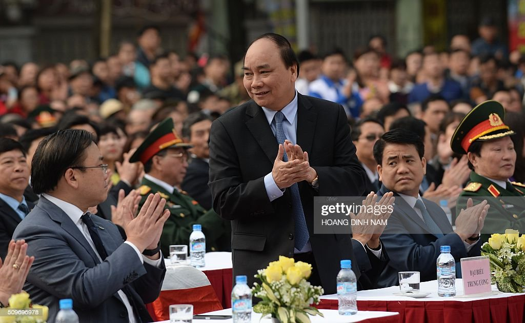 Politburo member and first Deputy Prime Minister Nguyen Xuan Phuc (C) raises up to greet the audience as he attends a ceremony marking the 227th anniversary of the Vietnam's Dong Da-Ngoc Hoi victory over China's Qing dynasty's troops in 1789 at a memorial monument to Vietnamese King Quang Trung (1788-1792), winner of the war, in Hanoi on February 12, 2016. AFP PHOTO / HOANG DINH Nam / AFP / HOANG DINH NAM