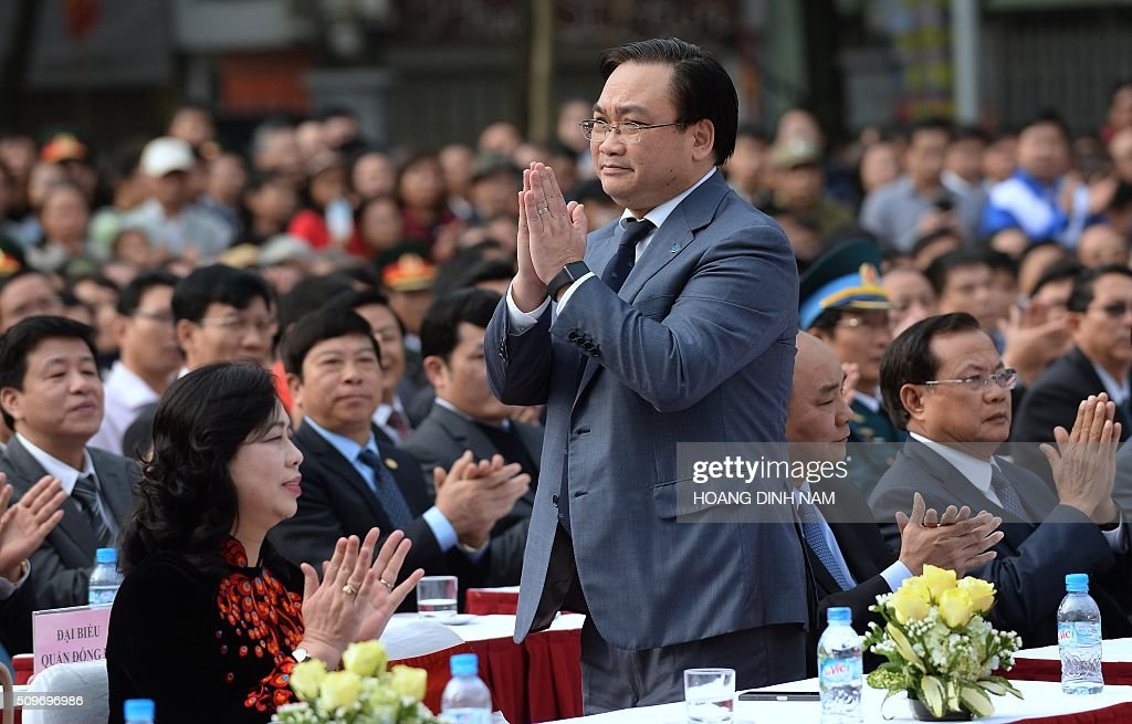 Politburo member and newly elected Party Chief for Hanoi Hoang Trung Hai (C) stands up to greet the audience as he attends a ceremony marking the 227th anniversary of the Vietnam's Dong Da-Ngoc Hoi victory over China's Qing dynasty's troops in 1789 at a memorial monument to Vietnamese King Quang Trung (1788-1792), winner of the war, in Hanoi on February 12, 2016. AFP PHOTO / HOANG DINH Nam / AFP / HOANG DINH NAM