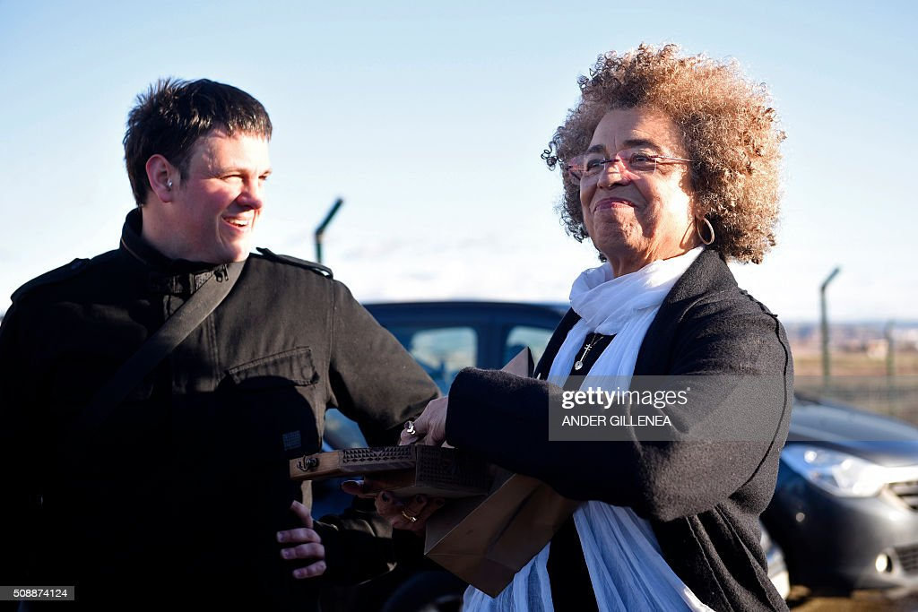 US political activist Angela Yvonne Davis (R) receives a present from Hodei Otegi, the son of the imprisoned leader of the Basque Patriotic Left movement Arnaldo Otegi outside the 'Centro Penitenciario de Logrono' prison, after Davis' vain attempt to visit the Basque politician on February 7, 2016, in the northern Spanish city of Logrono. Although Angela Davis had received the permission to visit Otegi, the prison of Logrono finally denied it. Arnaldo Otegi is imprisoned since 2009 and will be released on March 1, 2016. AFP PHOTO / ANDER GILLENEA / AFP / ANDER GILLENEA