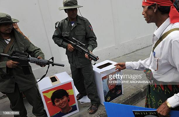 A political activist approaches mock ballot boxes as colleagues dressed as Myanmar soldiers raise their rifles during a mock vote as part of a...