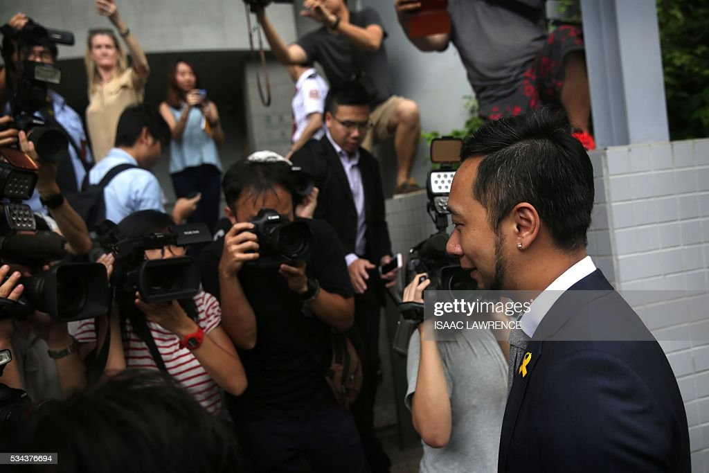 Political activist Ken Tsang (R) is surrounded by members of the media as he arrives at the Kowloon city court to receive his verdict, in Hong Kong on May 26, 2016. A Hong Kong pro-democracy activist who was allegedly beaten by police in an attack captured by television cameras and beamed around the world was found guilty of assaulting and resisting police officers on May 26. / AFP / ISAAC