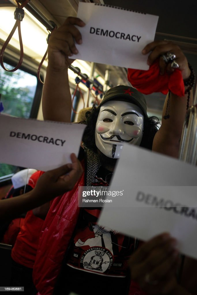 A political activist wears an anonymous mask and holds up a sign stating 'DEMOCRACY' as he travels on public transport for a political rally on May 25, 2013 in Kuala Lumpur, Malaysia. Thousands of supporters of Pakatan Rakyat (People's Pact/People's Alliance) gathered to voice their dissatisfaction over alleged election fraud in Malaysia's 13th General election result.