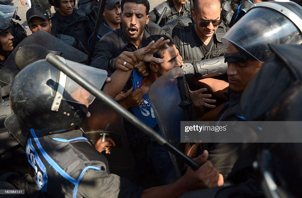 Political activists and supporters of 28-year-old blogger Khaled Said who died following police questioning before the revolution in 2010, clash with police outside a court in Egypt's northern coastal city of Alexandria on October 1, 2013 during the trial of Egyptian police officers Awad Ismail Suleiman and Mahmud Salah Amin accused of using excessive force and killing Said. The death of the Egyptian youth sparked demonstrations in Egypt, in the most high profile case to have dominated the headlines at the time. AFP PHOTO / STR