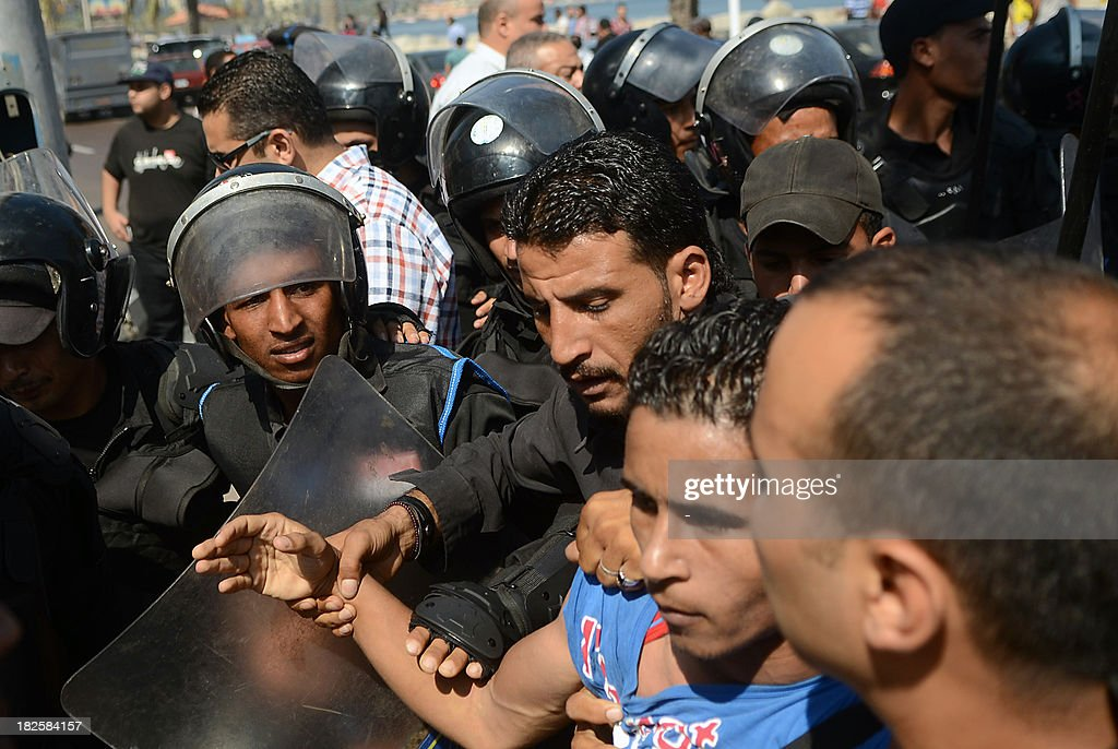 Political activists and supporters of 28-year-old blogger Khaled Said who died following police questioning before the revolution in 2010, clash with police outside a court in Egypt's northern coastal city of Alexandria on October 1, 2013 during the trial of Egyptian police officers Awad Ismail Suleiman and Mahmud Salah Amin accused of using excessive force and killing Said. The death of the Egyptian youth sparked demonstrations in Egypt, in the most high profile case to have dominated the headlines at the time.