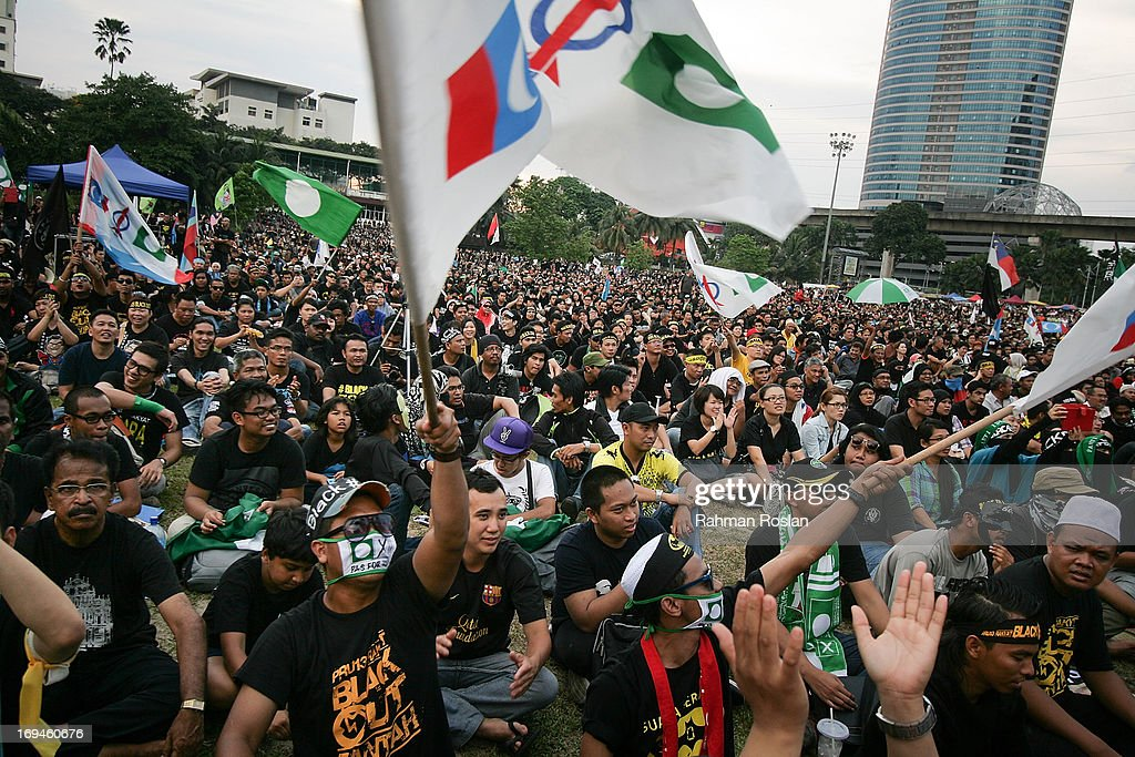 Political activistsshout slogans and wave flags and banners during a political rally against election fraud on May 25, 2013 in Kuala Lumpur, Malaysia. Thousands of supporters of Pakatan Rakyat (People's Pact/People's Alliance) gathered to voice their dissatisfaction over alleged election fraud in Malaysia's 13th General election result.