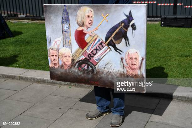 TOPSHOT Political artist Kaya Mar holds a painting depicting the faces of British Prime Minister Theresa May British Foreign Secretary Boris Johnson...