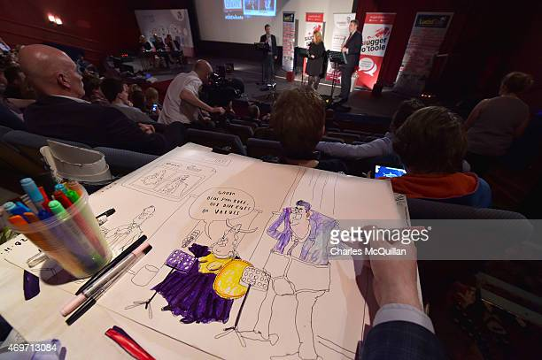 Political cartoonist and artist Brian John Spencer sketches a drawing of Alliance party candidate Naomi Long and DUP party candidate Gavin Robinson...