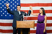 Political couple at podium by American flag