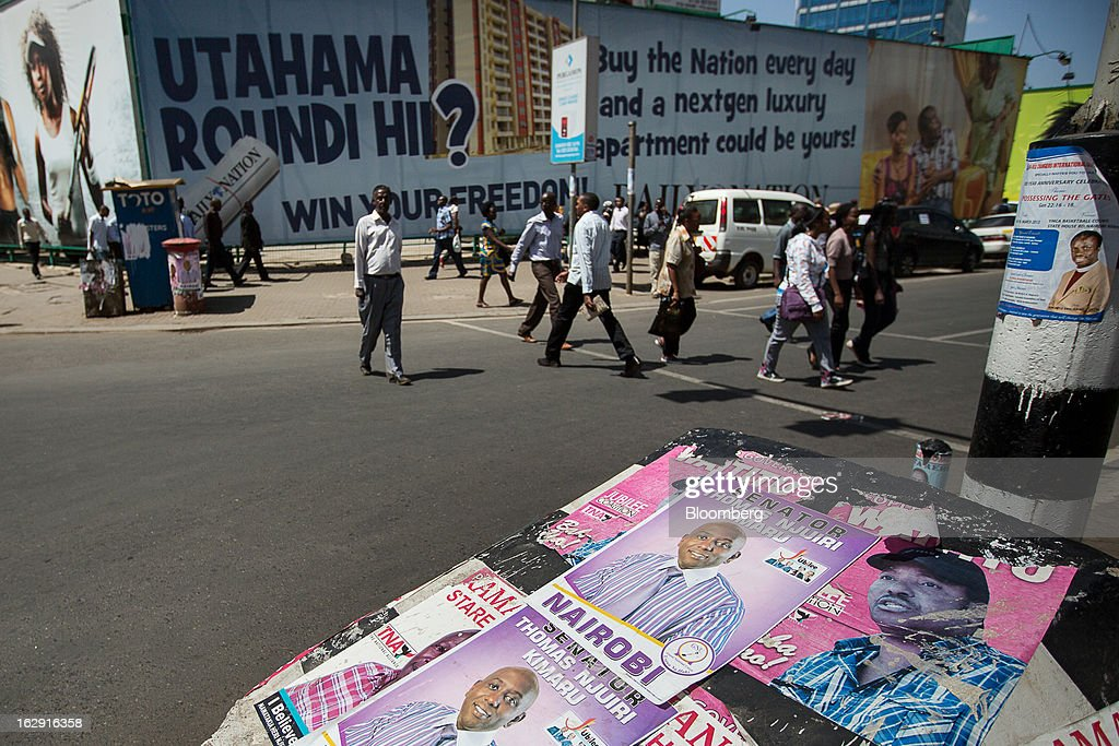 Political election posters for Senator Thomas Njuiri Kimaru are seen on the roadside as pedestrians cross a street in Nairobi, Kenya, on Friday, March 1, 2013. Next week's presidential vote will be the first since disputed elections in 2007 triggered ethnic fighting in which more than 1,100 people died and another 350,000 fled their homes. Photographer: Trevor Snapp/Bloomberg via Getty Images