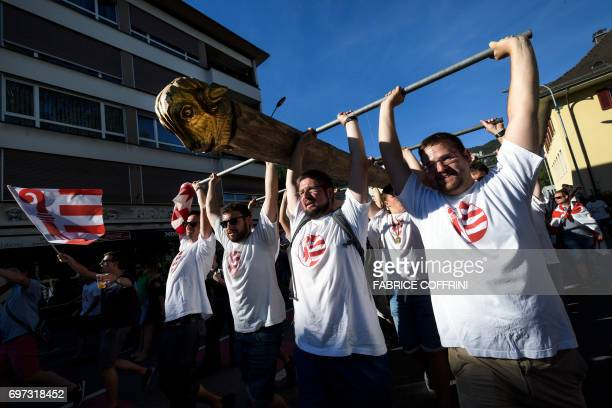 Political group members raise a battering ram symbol of separatism during a demonstration after the commune of Moutier voted to join primarily...