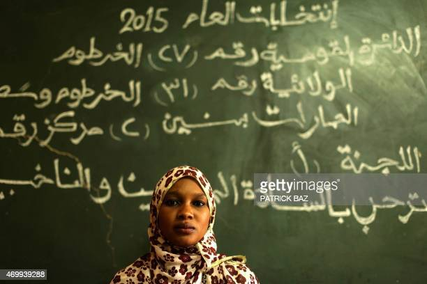 A political party observer sits under a billboard at a polling station in the Sudanese capital Khartoum on April 16 2015 Sudan extended nationwide...