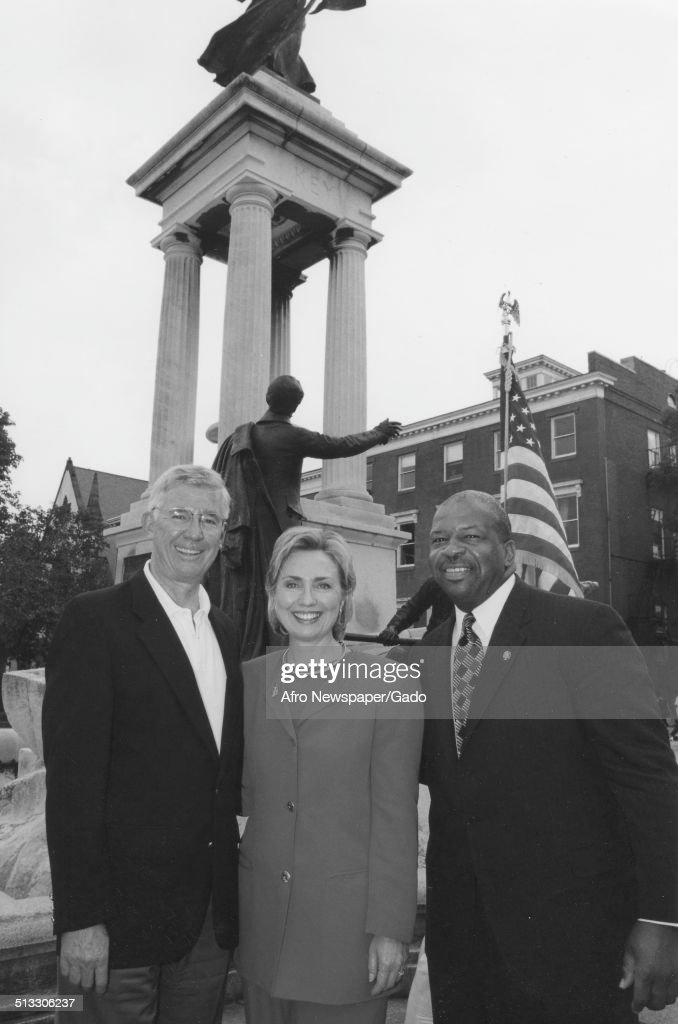 Politician and former First Lady of the United States Hillary Clinton, 59th Governor of Maryland Parris Glendening and politician and Maryland congressional representative Elijah Cummings, with building, standing in a street, Maryland, 1995.
