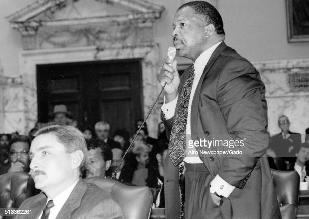 Politician and Maryland congressional representative Elijah Cummings speaking into a microphone during a meeting 1960