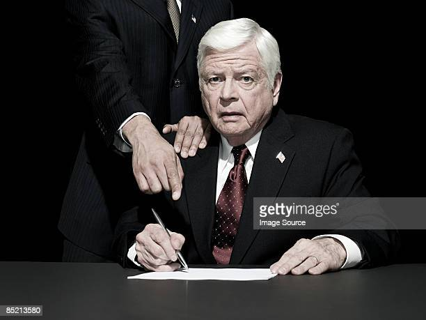 Politician being made to sign