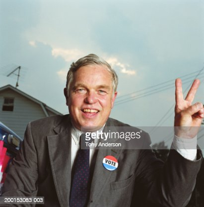 Politician giving 'victory' sign, portrait, close-up : Stock Photo