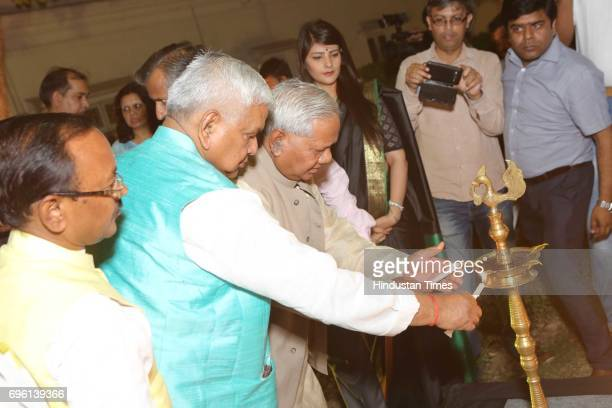 Politician Kariya Munda lights the lamp during the screening of a biography based on Munda's life a tribute to tribal leader and freedom fighter...