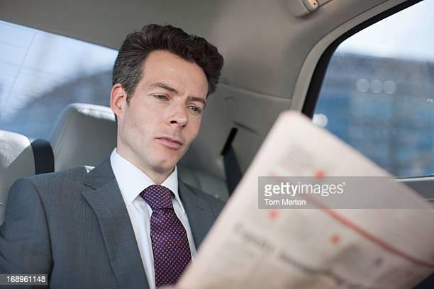 Homme politique lisant le journal dans backseat de voiture