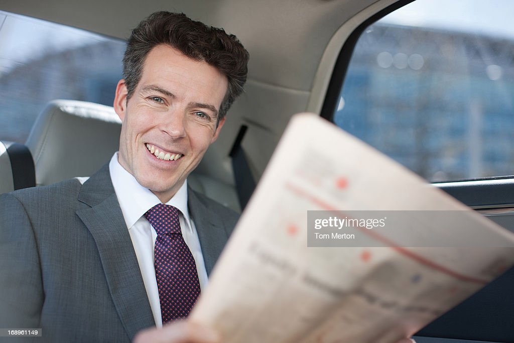 Politician reading newspaper in backseat of car : Stock Photo