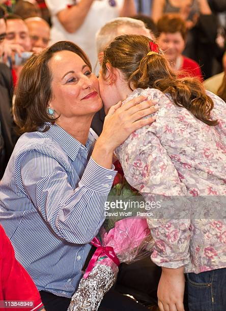 Politician Segolene Royal is presented with flowers by a young girl at a meeting held to honour the achievements of former French President Francois...