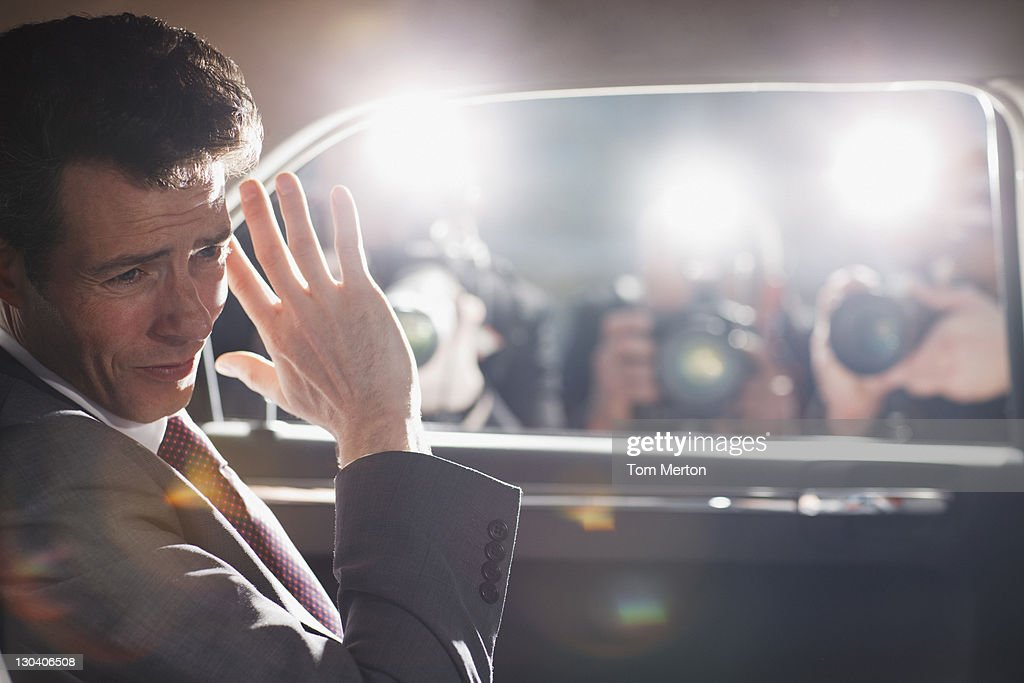 Politician shielding himself from paparazzi : Stock Photo