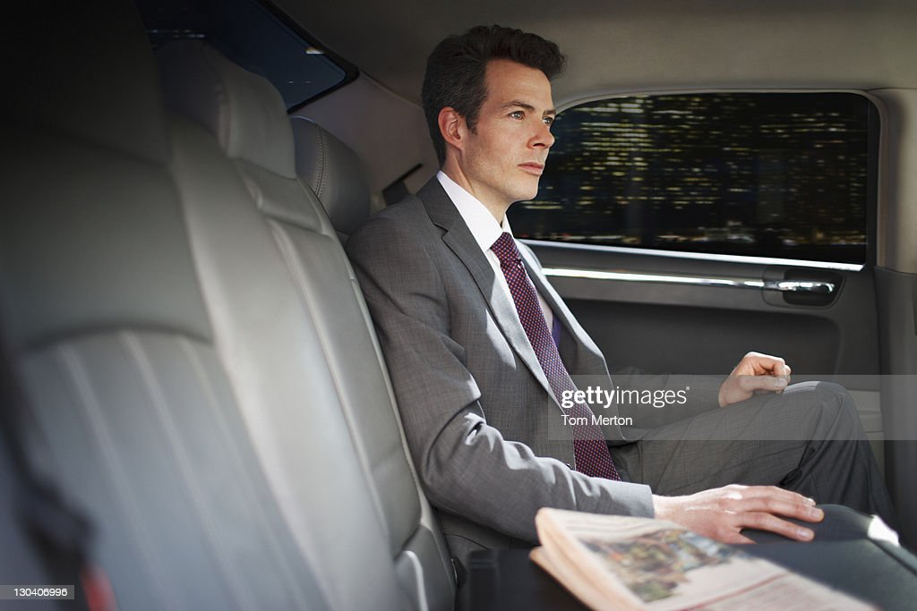 Politician sitting in backseat of car : Stock Photo