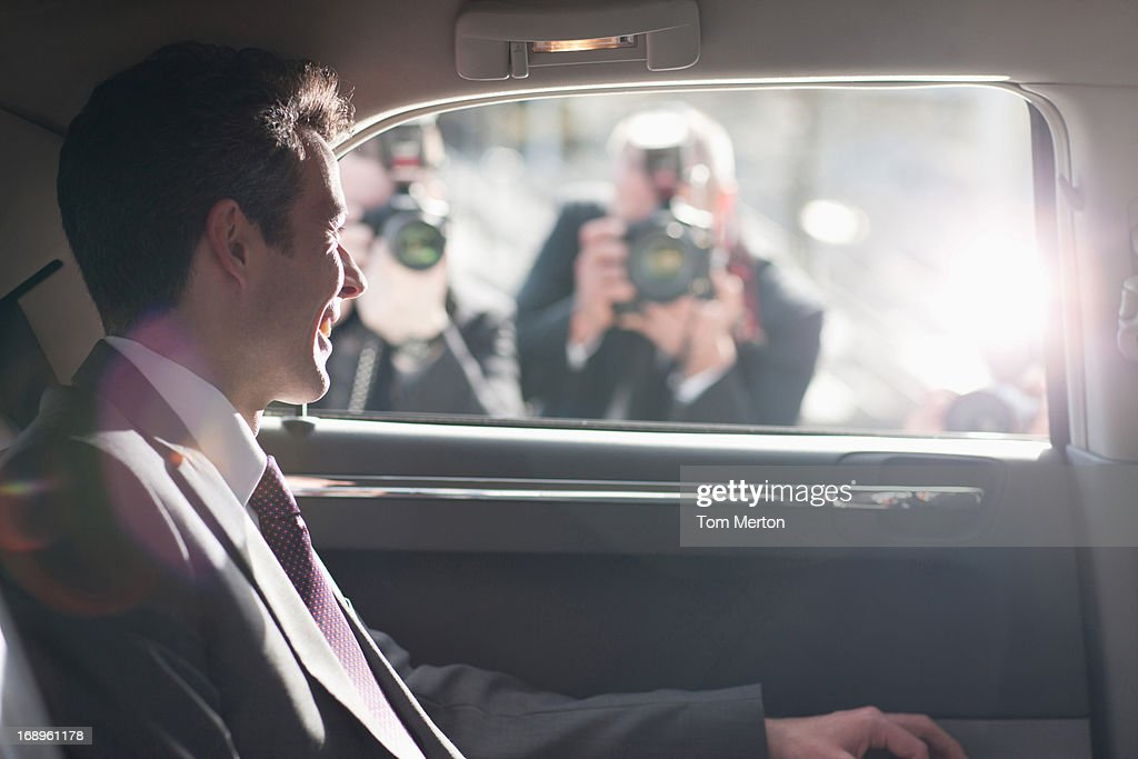 Politician smiling for paparazzi in backseat of car : Stock Photo