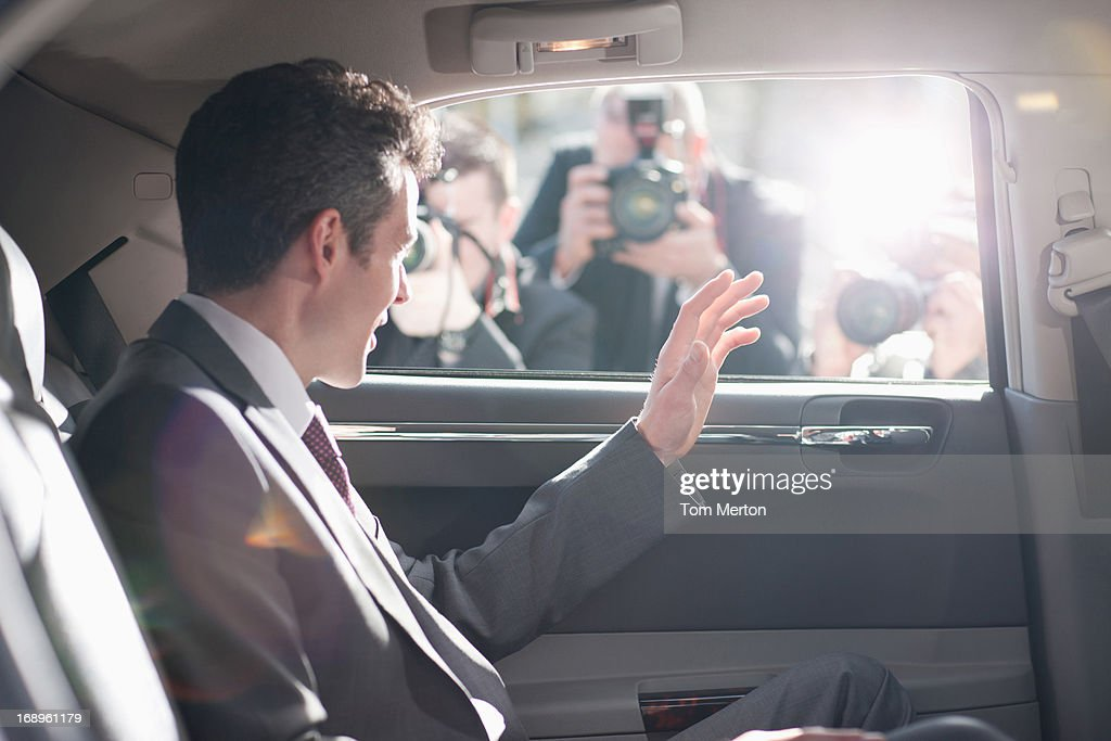 Politician waving from backseat of car : Stock Photo
