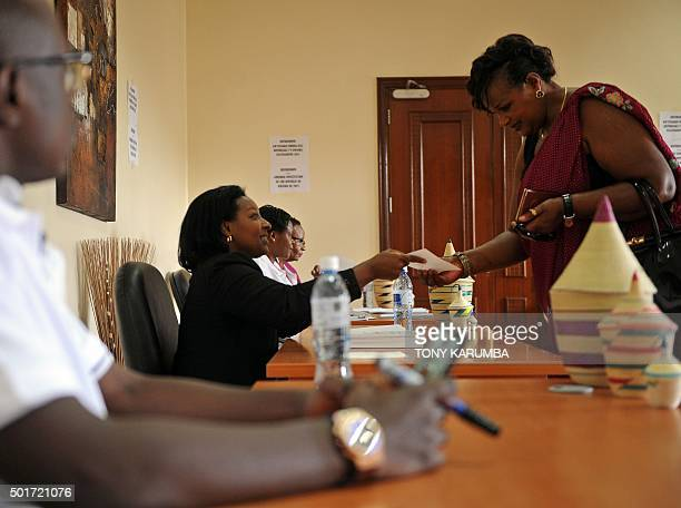 A poll clerk hands gives ballot papers to a registered Rwandan voter at a polling station on December 17 2015 at the Rwandan High Commission in...