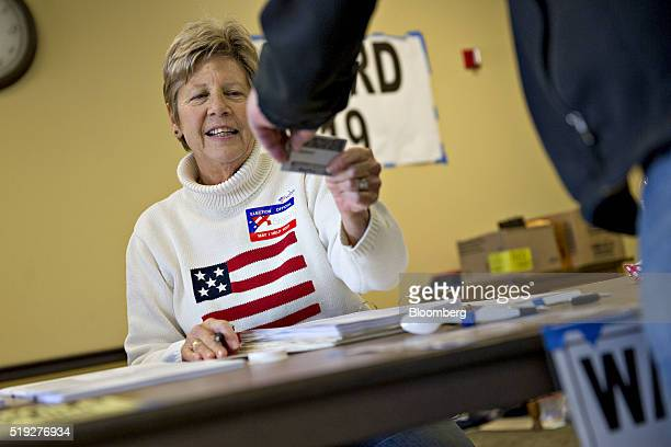 A poll worker checks the identification of a resident at polling location during the presidential primary vote in Waukesha Wisconsin US on Tuesday...