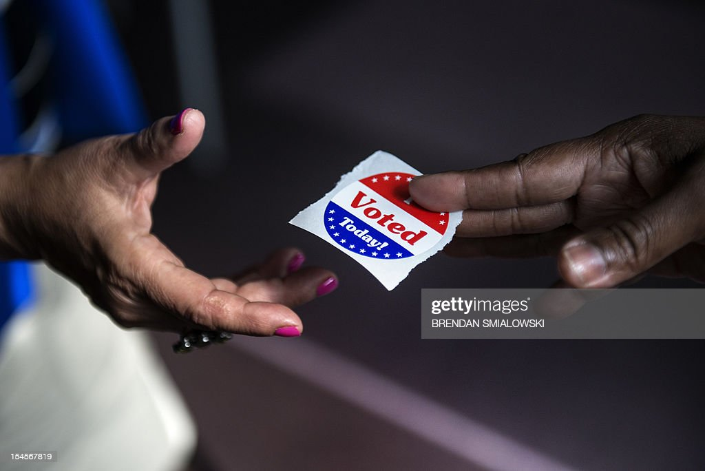 A poll worker hands out 'I Voted Today' stickers during the first day of early voting October 22 2012 in Washington DC Citizens of the District of...