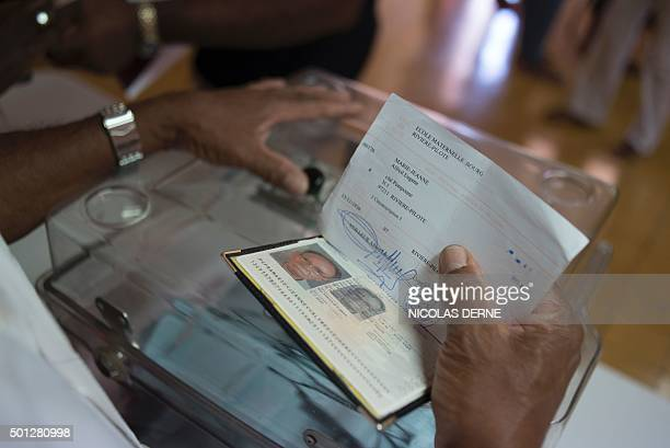 A poll worker holds the voter card and passport of Alfred MarieJeanne candidate of the 'Gran Sanble pou ba Peyia an Chans' list for the French...