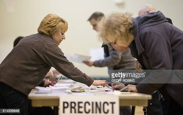 A poll worker instructs voters at a polling station in Warren Michigan March 8 2016 US voters cast ballots in White House primaries in Michigan and...