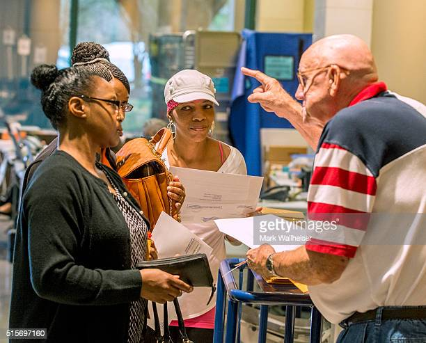 Poll worker Ira Sewell right explains the voting procedures to voters before they cast their ballots in the presidential primary at the Leon County...