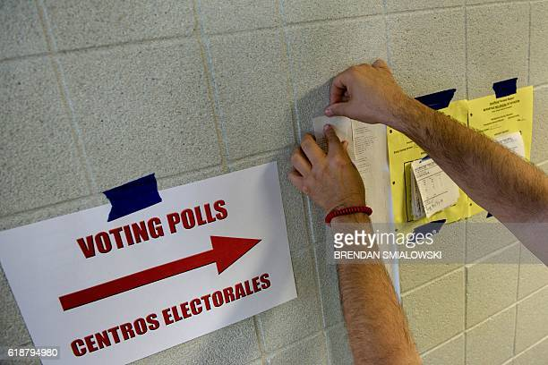 A poll worker posts receipts from vote counting machines showing they have been properly prepared for the days voting at the Activity Center at...
