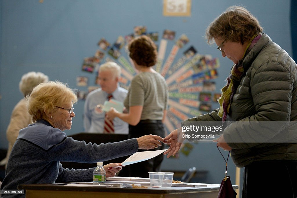 A poll worker takes a colored chip from a voter as they choose their ballots at the Bishop Leo E. O'Neil Youth Center February 9, 2016 in Manchester, New Hampshire. New Hampshire voters finally go to the polls in the first in the nation primary state that begins the long election season.