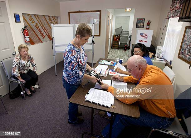 Poll workers check the identification of Suzanne Grant in the tiny precinct of Smith Creek on November 6 2012 in Sopchoppy Florida The swing state of...