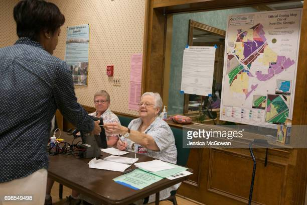 Poll workers Rebecca Lynn Medlin Pat Blair pass out ballot cards to voters at the Doraville City Hall for Georgia's 6th Congressional District runoff...