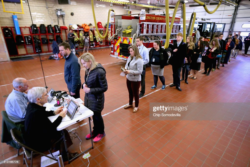 Poll workers verify voters' photo indentification cards before they are allowed to cast a ballot inside the Arlington County Fire Station 10 during...