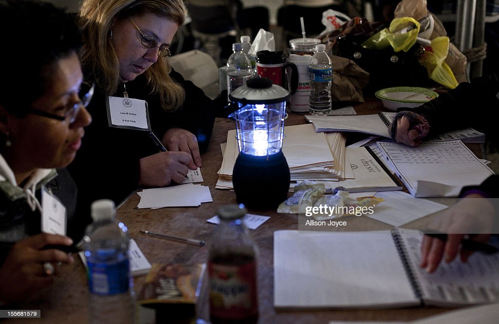 Poll workers work by generator lights and a small battery run portable light in the presidential elections in a tent in Midland Beach November 6, 2012 in the Staten Island borough of New York City. As Staten Island continues to recover from Superstorm Sandy, a few polling stations have been relocated due to power outages or ongoing use as an evacuation center.