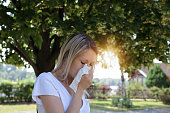 Pollen allergy. Woman sneezing in a tissue outdoors